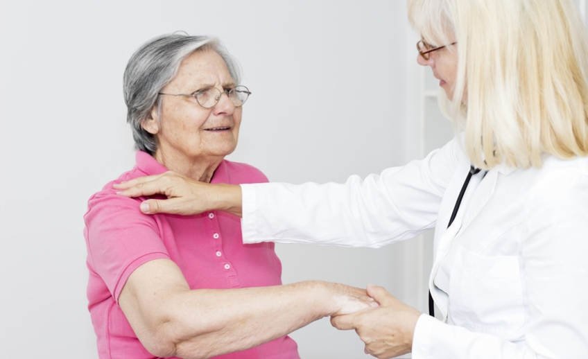Female doctor looking at her female patient and touching senior women shoulder, giving  to her physical therapy.